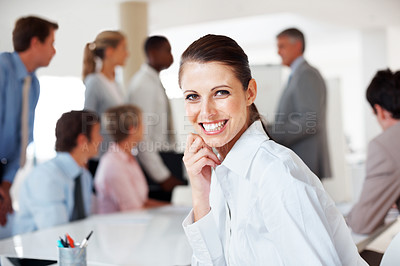 Buy stock photo Beautiful young businesswoman smiling with her team working on project in background