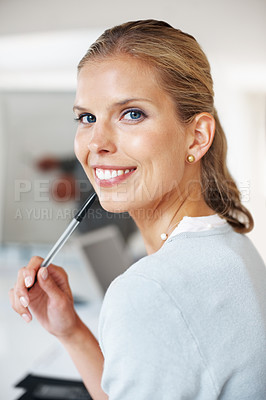 Buy stock photo Portrait of a confident young businesswoman smiling and holding a pen at office