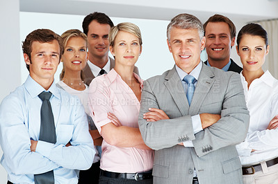 Buy stock photo Portrait of a confident mature businessman leading a business team at office