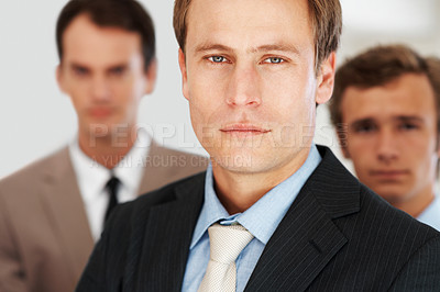 Buy stock photo Closeup portrait of a handsome young businessman with his colleagues in background