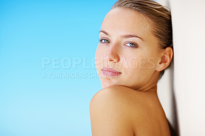 Buy stock photo Young topless model leaning against a wall with the blue sky as the background