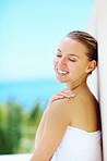 Happy cute female in towel leaning against a wall outside