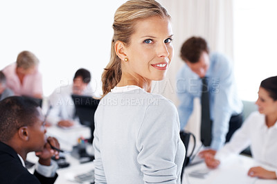 Buy stock photo Happy young businesswoman looking behind and her colleagues working at office