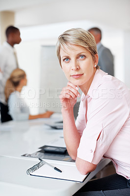 Buy stock photo Portrait of a confident young female executive looking at you with colleagues in background