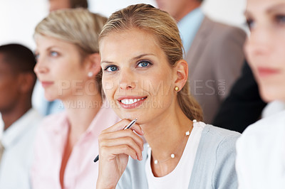 Buy stock photo Portrait of a smart young businesswoman smiling in a meeting with her colleagues