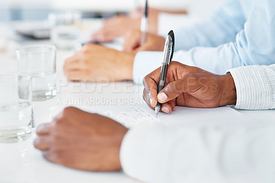 Buy stock photo Closeup of hands taking notes at a conference in the office with colleagues in background