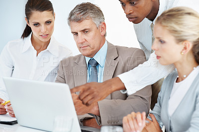 Buy stock photo Confident man discussing a project with colleagues pointing at laptop