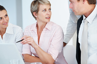 Buy stock photo Portrait of a smart young businesswoman discussing work with her colleagues at office