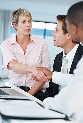 Buy stock photo Portrait of a smart young businesswoman shaking hand with her colleague at office
