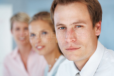 Buy stock photo Portrait of a confident young businessman looking with his colleagues behind at office