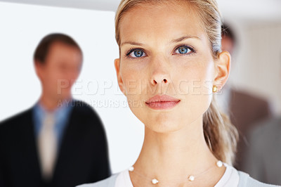 Buy stock photo Portrait of a confident young businesswoman looking with an attitude and her colleagues behind at office