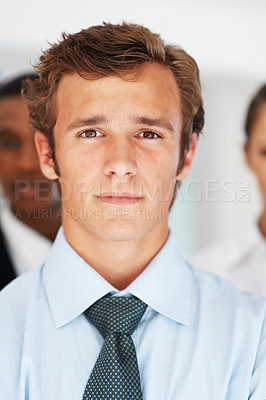 Buy stock photo Closeup portrait of handsome young male business executive with people in background