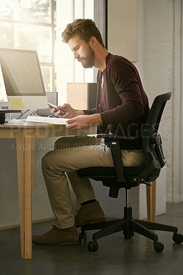 Buy stock photo Shot of a businessman using his cellphone while reading a book