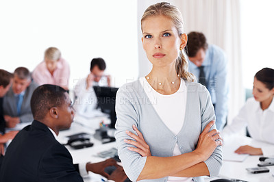 Buy stock photo Portrait of a young businesswoman looking wth an attitude and her colleagues working behind at office
