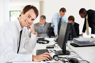 Buy stock photo Portrait of a successful young businessman smiling while working on the computer at the office