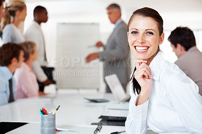 Buy stock photo Portrait of a happy young businesswoman smiling with colleagues having presentation in background