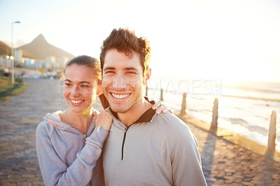 Buy stock photo A young couple in jogging wear standing on the promenade at sunset