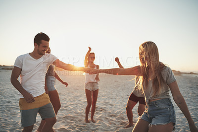 Buy stock photo Shot of a young group of friends dancing on the beach