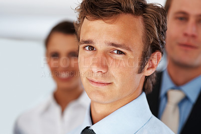 Buy stock photo Closeup of a male business executive standing with team at office