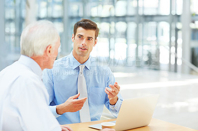 Buy stock photo Cropped shot of two businessmen discussing information on a laptop while enjoying a cup of coffee