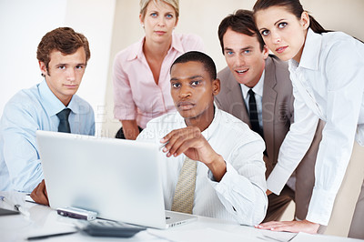Buy stock photo Successful group of young businesspeople working together on laptop at board room