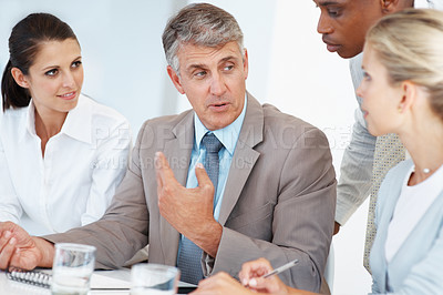 Buy stock photo Successful senior executive in conversation with his team during a meeting