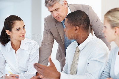 Buy stock photo Senior businessman listening to his colleagues during a staff meeting