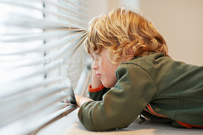 Buy stock photo A young boy peeping through a window
