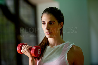 Buy stock photo Cropped shot of a young woman working out with dumbbells at the gym