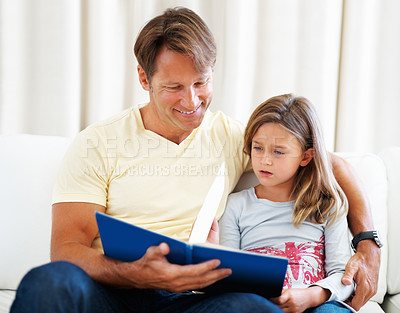 Buy stock photo Father and daughter sitting together on a sofa and reading story book