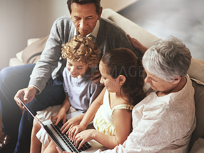 Buy stock photo Shot of an elderly couple and their grandchildren sitting together and using a laptop