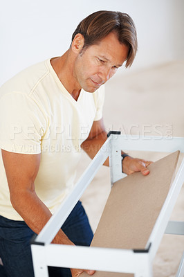 Buy stock photo Portrait of hard working man building a shelf at home