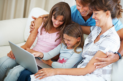 Buy stock photo Family of four sitting on a sofa using laptop and smiling