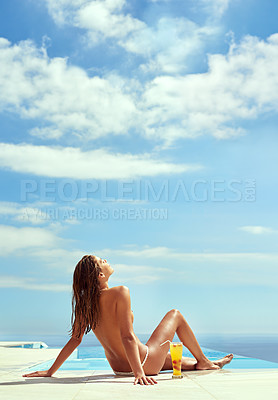 Buy stock photo Shot of a beautiful young woman sunbathing topless by a swimming pool