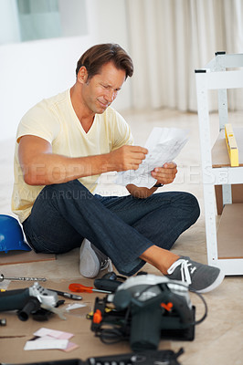 Buy stock photo Full length of man reading the instructions to build a shelf