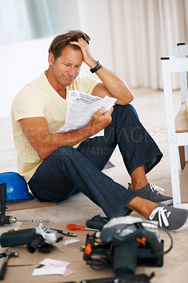 Buy stock photo Full length of man sitting with hand in hair while reading instructions to build a shelf
