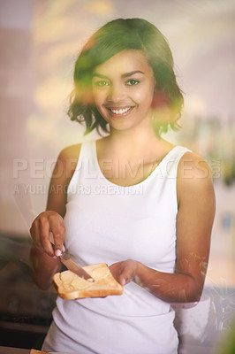 Buy stock photo Shot of a young woman spreading butter onto toast