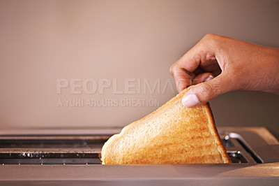 Buy stock photo Cropped shot of a woman taking toast out of a toaster