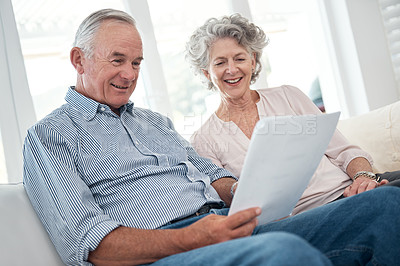 Buy stock photo Shot of a senior couple reading through documents at home