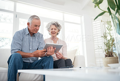 Buy stock photo Cropped shot of a senior couple using a digital tablet at home