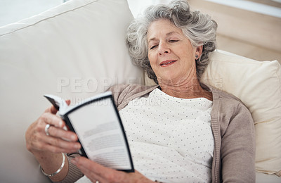 Buy stock photo Shot of a senior woman reading a book while lying on the sofa
