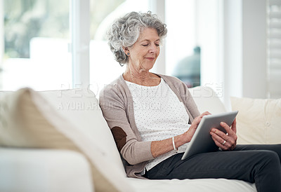 Buy stock photo Cropped shot of a senior woman using a digital tablet at home