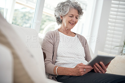 Buy stock photo A senior woman using a digital tablet while sitting on the sofa at home