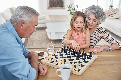 Buy stock photo Shot of a little girl playing chess with her grandparents
