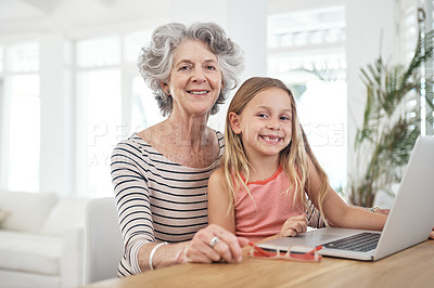Buy stock photo Shot of a little girl and her grandmother using a laptop at home