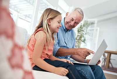 Buy stock photo Shot of a little girl and her grandfather using a laptop at home