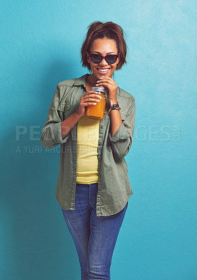 Buy stock photo Shot of a young woman sipping on juice against a blue background