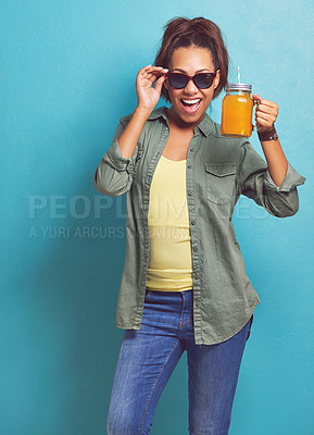 Buy stock photo Portrait of a young woman holding a juice jug against a blue background