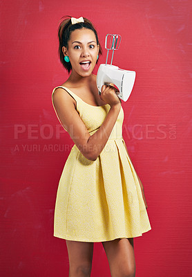 Buy stock photo Studio shot of a young woman holding an electric mixer against a red background