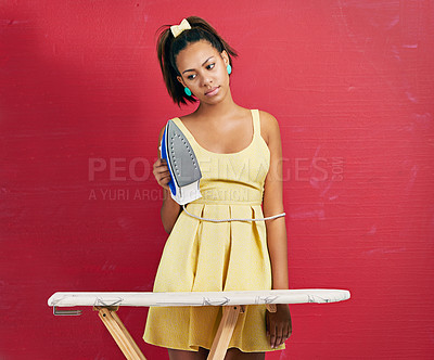 Buy stock photo Studio shot of a young woman doing the ironing against a red background